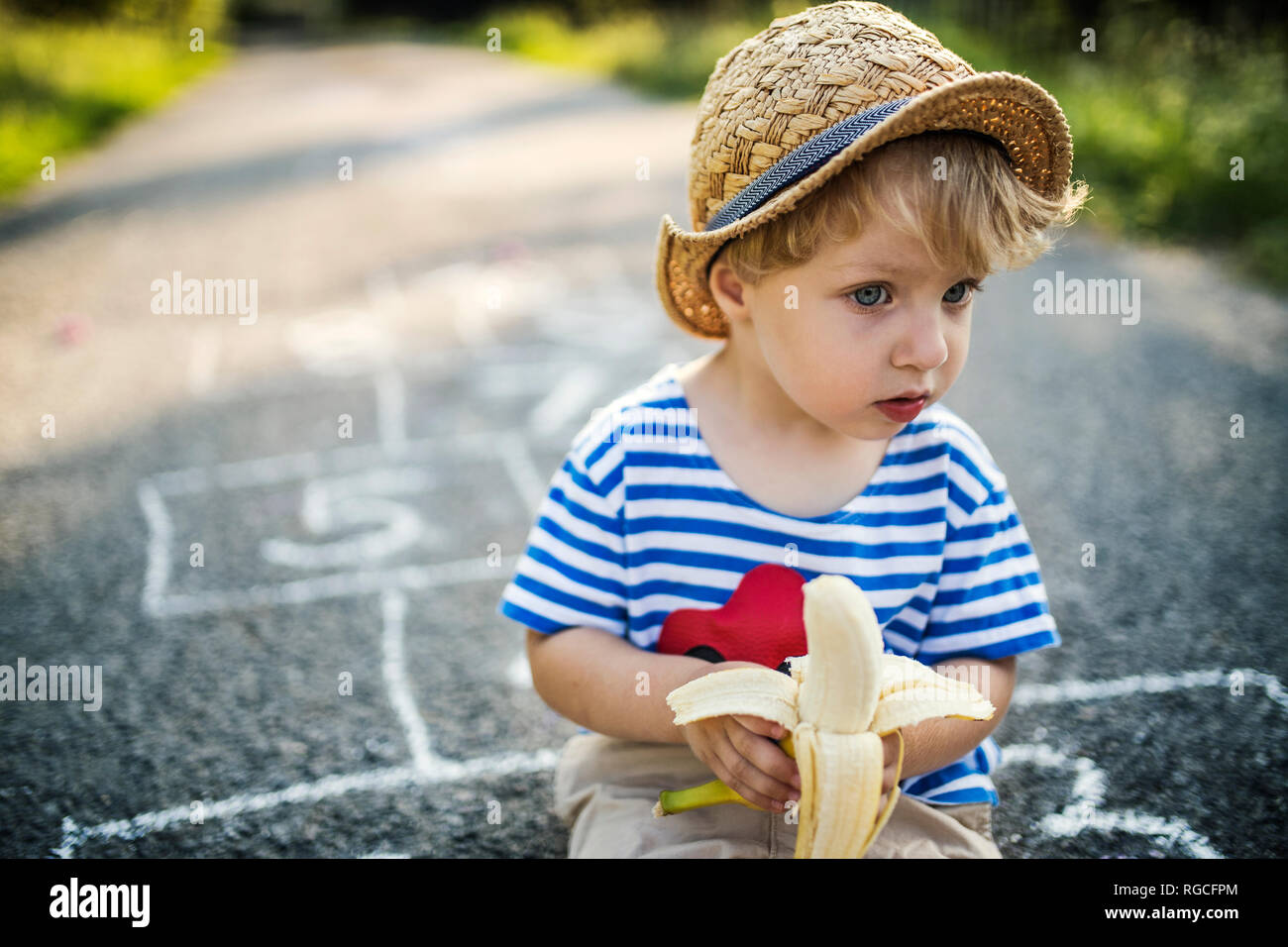 Portrait of toddler boy with banana sitting on the street watching something Stock Photo