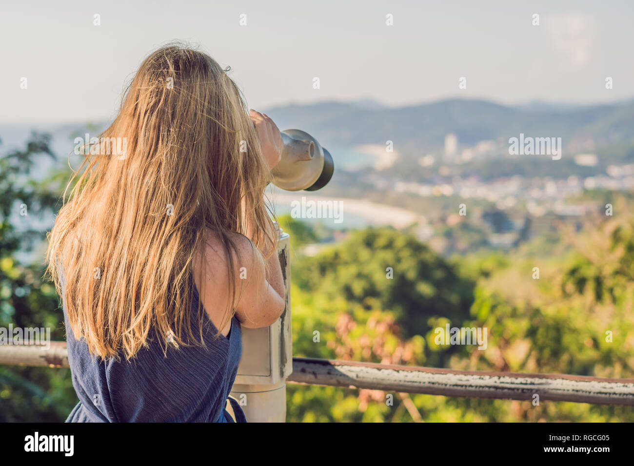 young beautiful blond woman enjoy the view with an coin operated binoculars. The water and the sky is blue. she wears a white dress and sunglasses - Stock Image