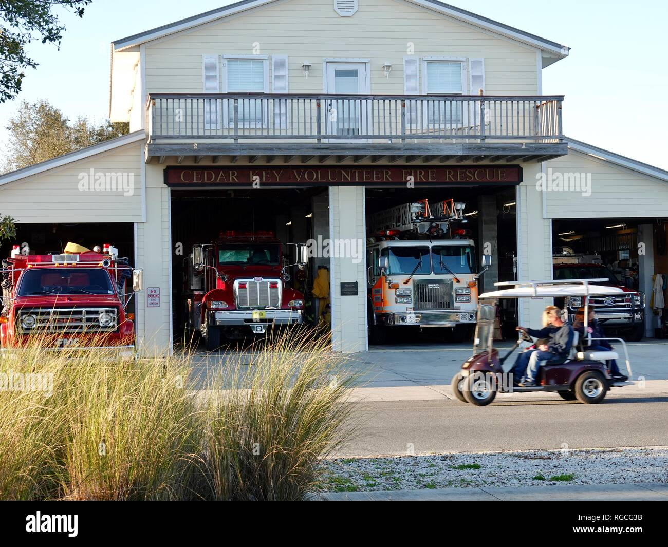 Couple in golf cart driving past the Cedar Key Volunteer Fire Rescue Department, Florida, USA. - Stock Image