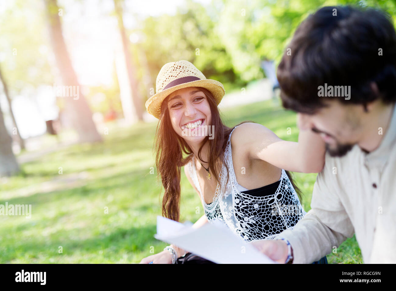 Portrait of laughing young woman  having fun in a park with her fellow student - Stock Image
