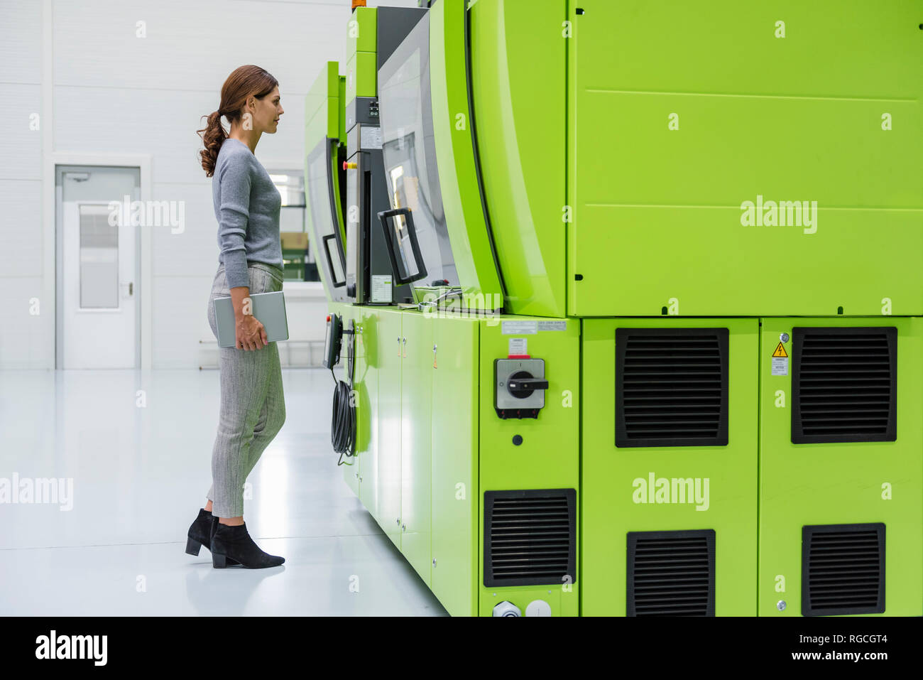 Businesswoman in high tech company controlling manufacturing machines - Stock Image