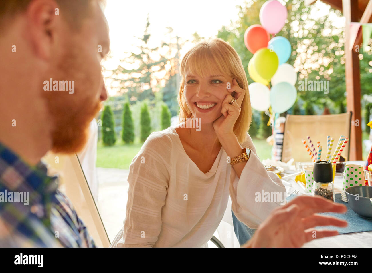 Smiling woman looking at man on a garden party - Stock Image