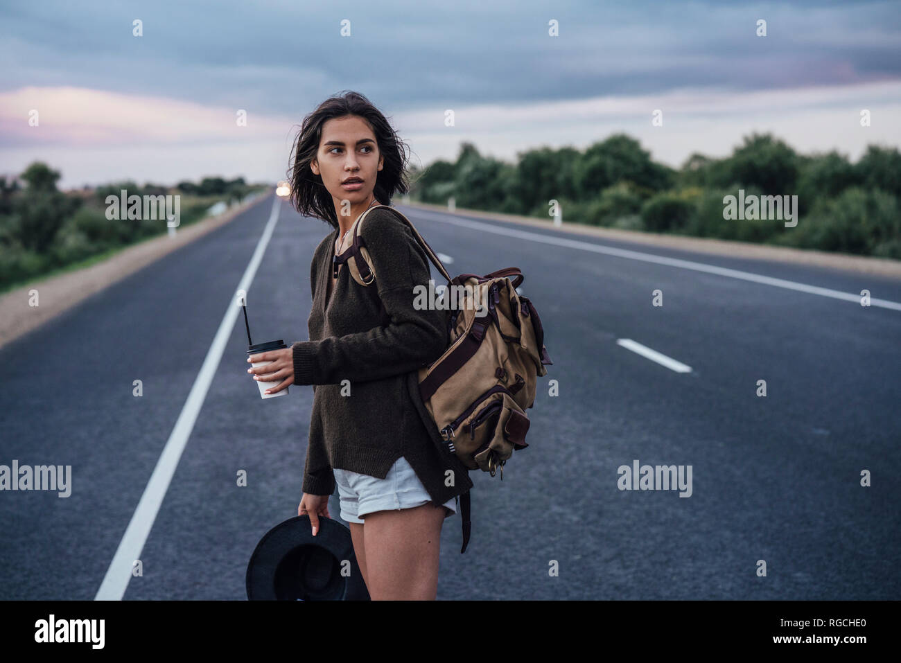 Portrait of young hitchhiking woman with backpack and beverage standing on lane Stock Photo