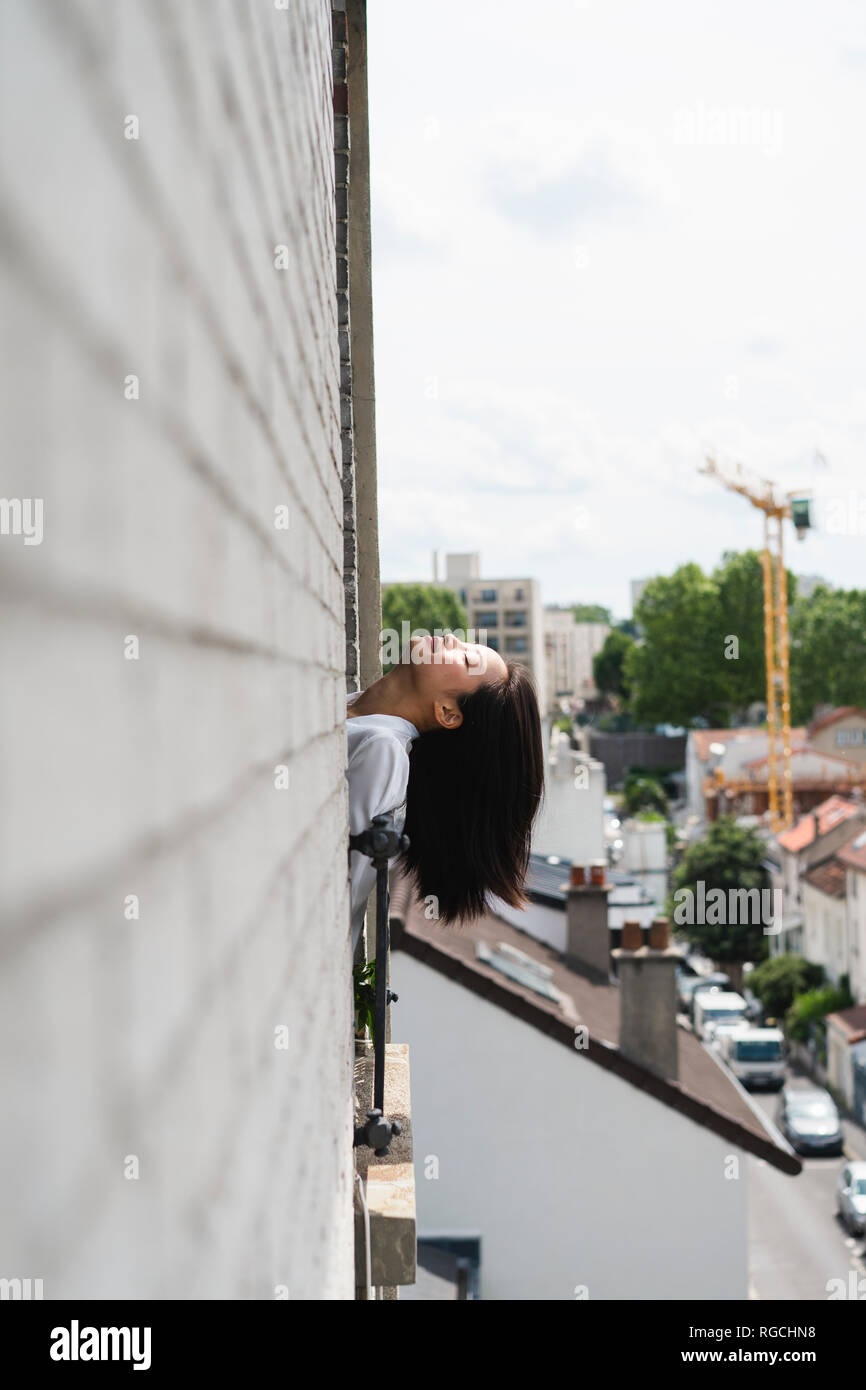 France, Paris, young woman leaning her head out of the window - Stock Image