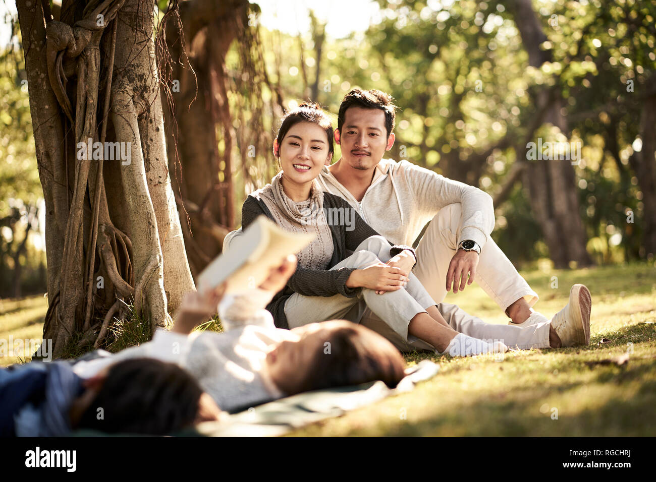 two asian children little boy and girl having fun lying on grass reading a book with parents sitting watching in background, focus on the parents in b Stock Photo