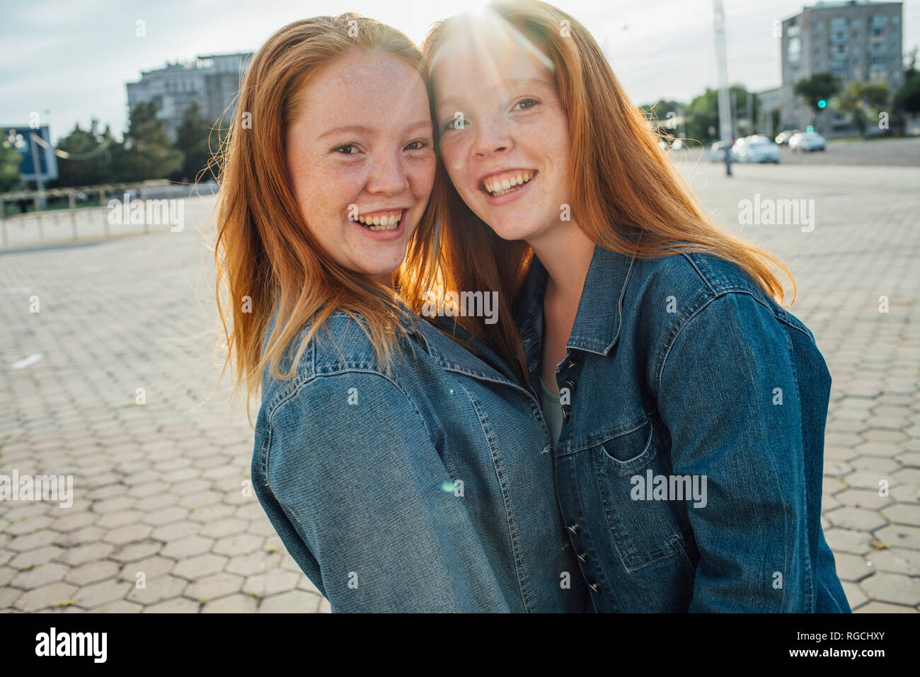 Smiling redheaded twins in the city, sunlight - Stock Image