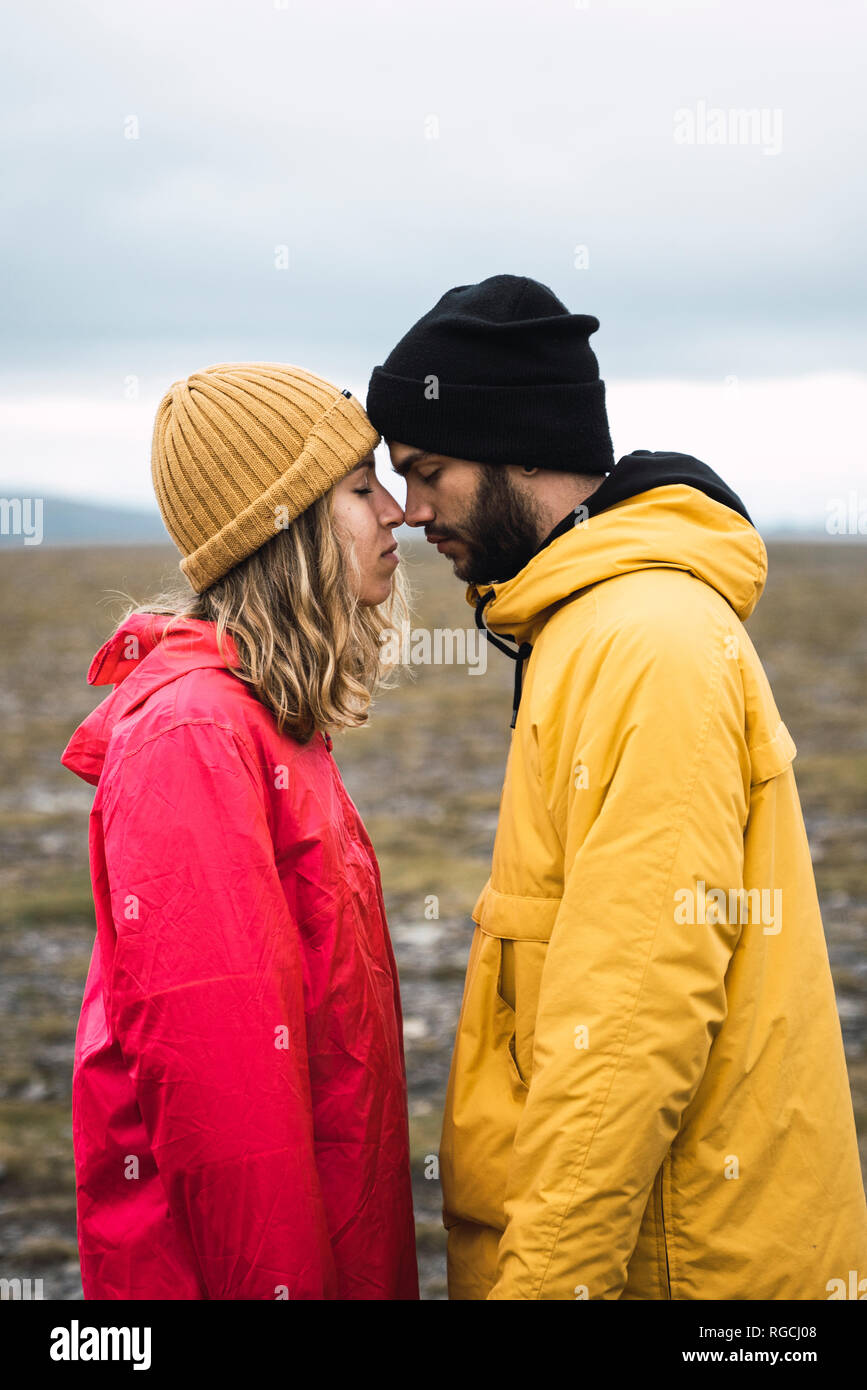Young couple rubbing affectionately noses, Lapland, Norway - Stock Image