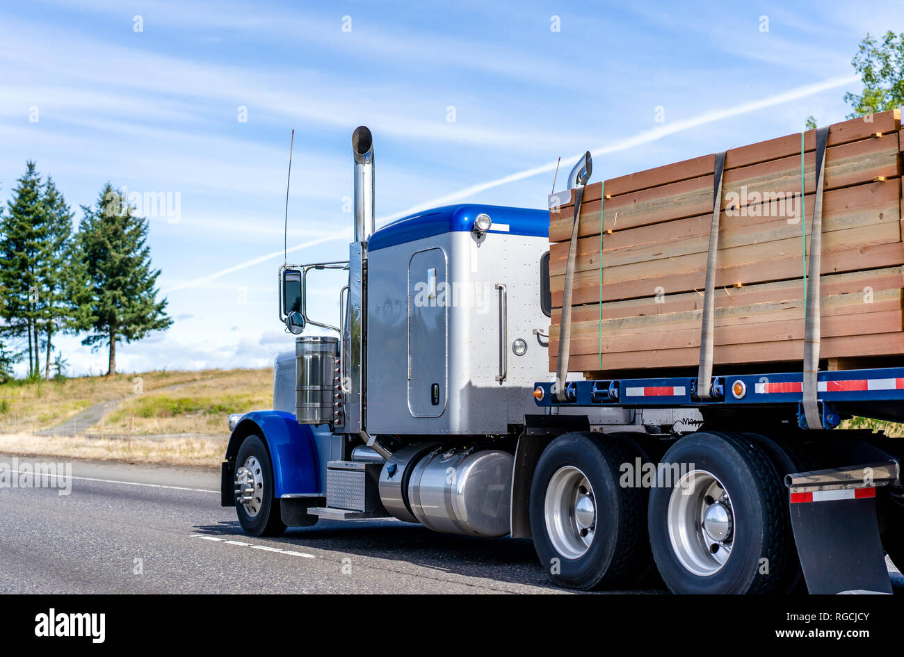 Big Rig Classic American Blue Bonnet Semi Truck Tractor With High Exhaust Pipes Transporting Stocked Up Lumber Wood On Flat Bed Semi Trailer Running O Stock Photo Alamy
