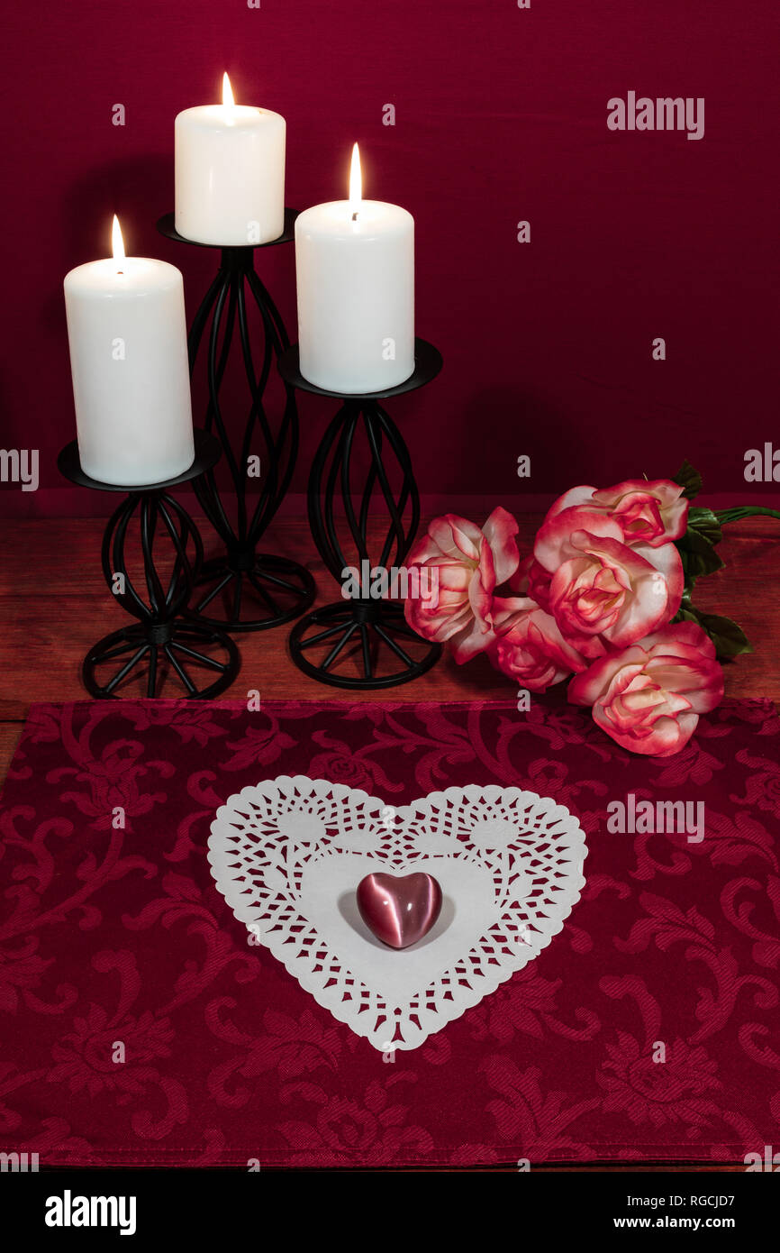 Heart shapped dollie and gemstone, three white candles in metal holoders and bouquet of orange and white roses on wooden table. Stock Photo