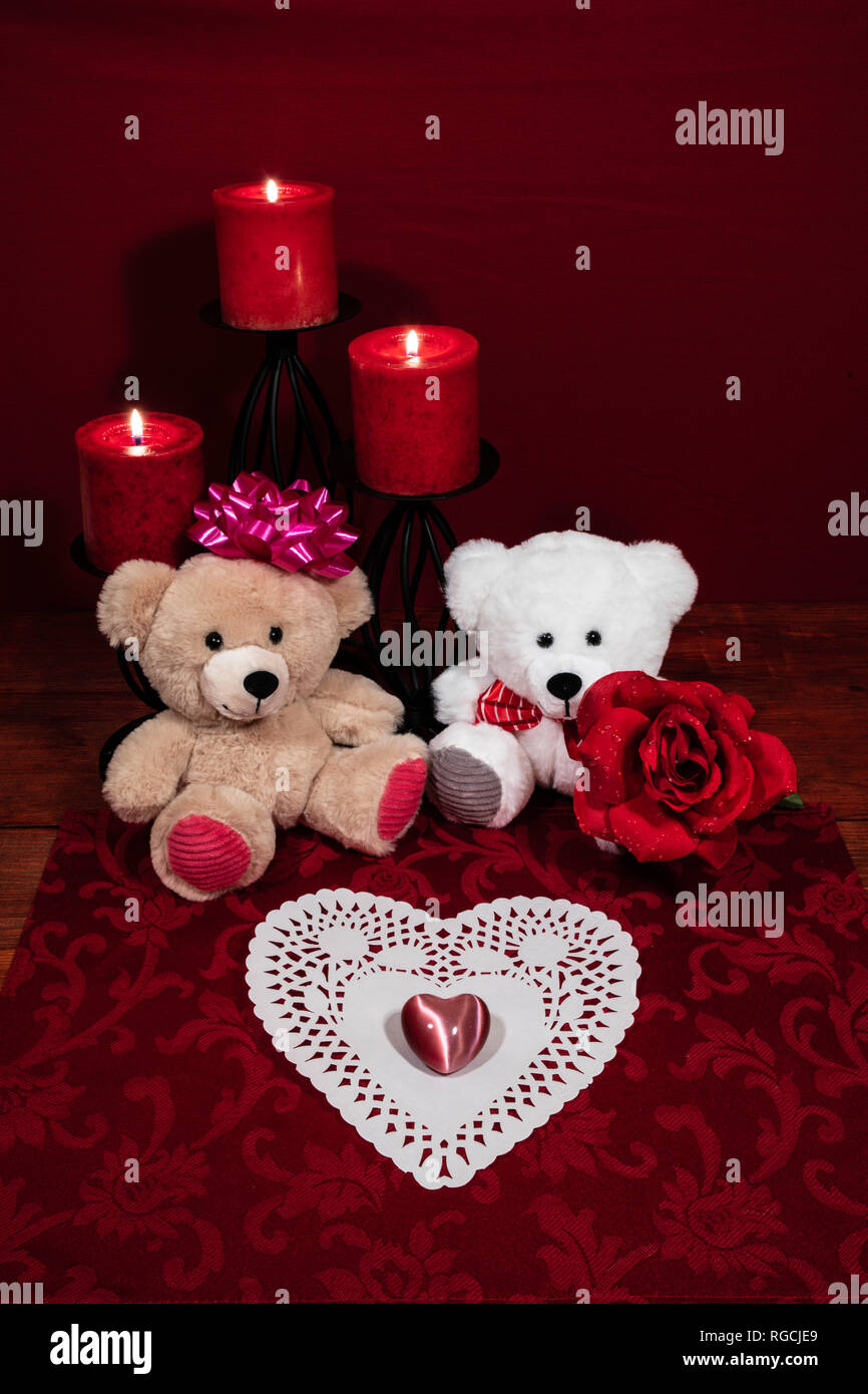 Heart shapped dollie and gemstone, three red candles in metal holders and red rose, two teddy bears on wooden table. Stock Photo