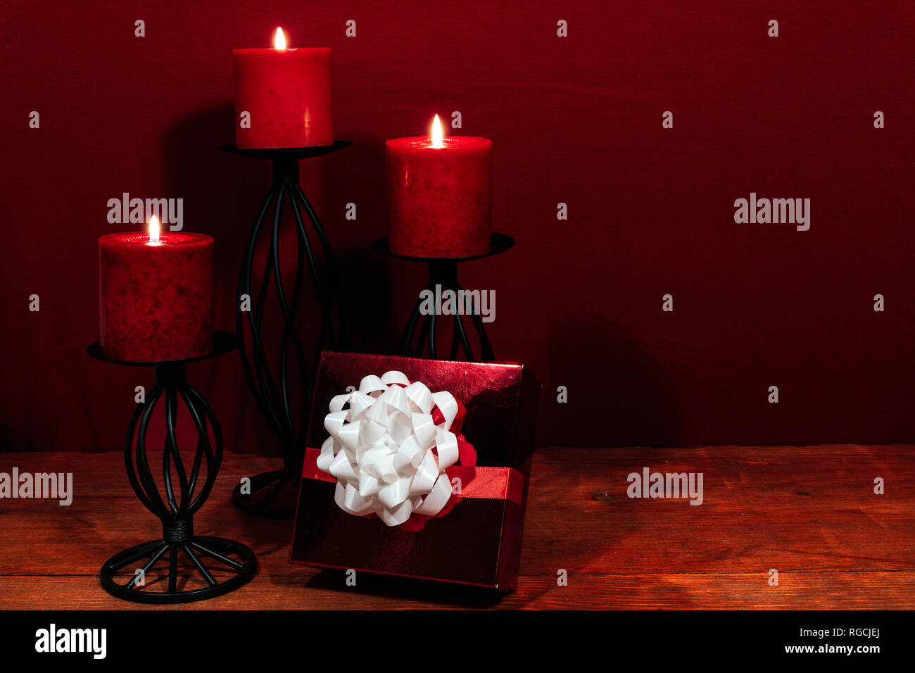 Three red candles in metal holders and red rose, present with white bow on wooden table. Stock Photo