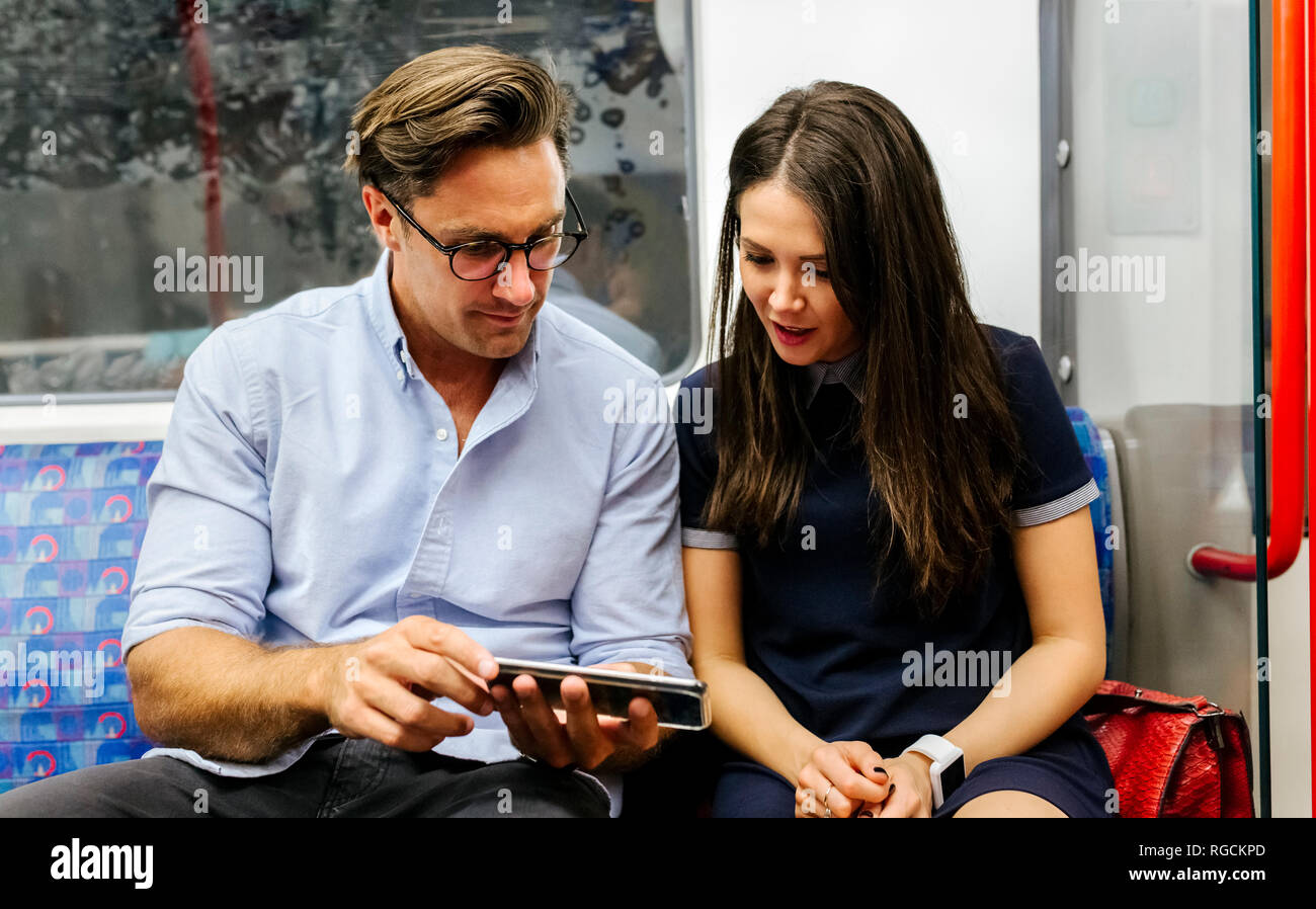 UK, London, couple sharing cell phone in subway - Stock Image