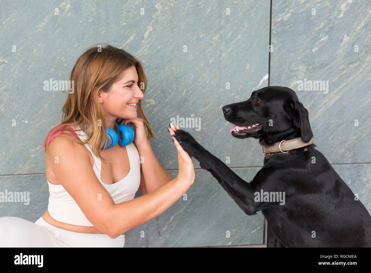 Happy young woman with her black dog - Stock Image