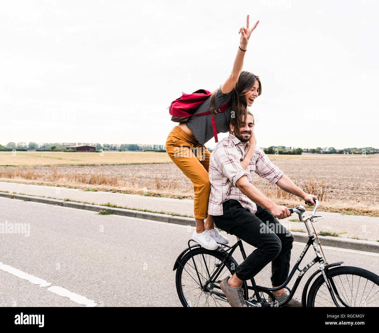 Happy young couple riding together on one bicycle on country road Stock Photo