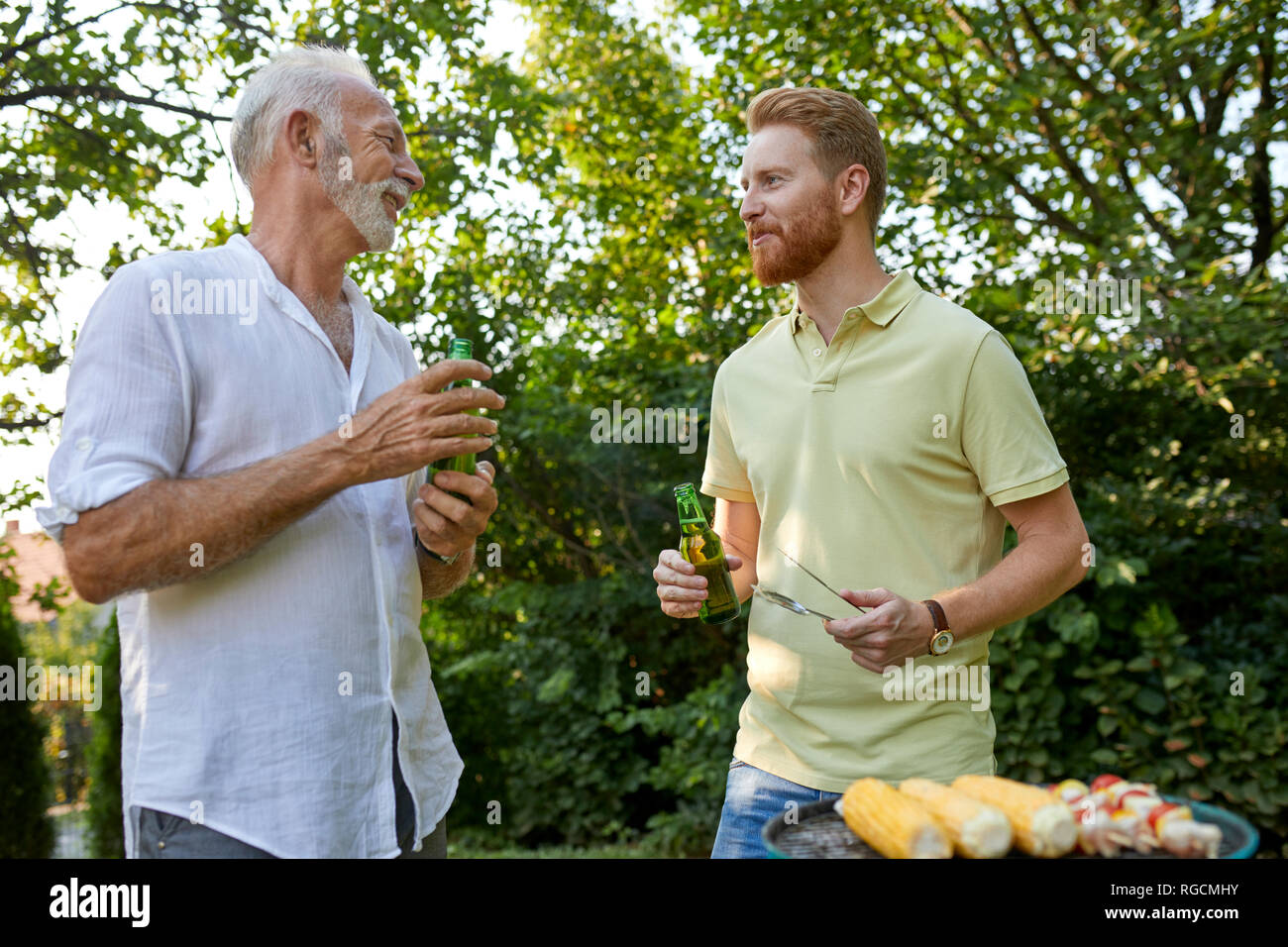 Senior father and adult son having a barbecue and talking in garden - Stock Image