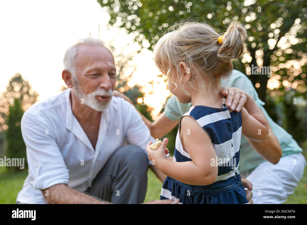 Grandparents with granddaughter in garden Stock Photo