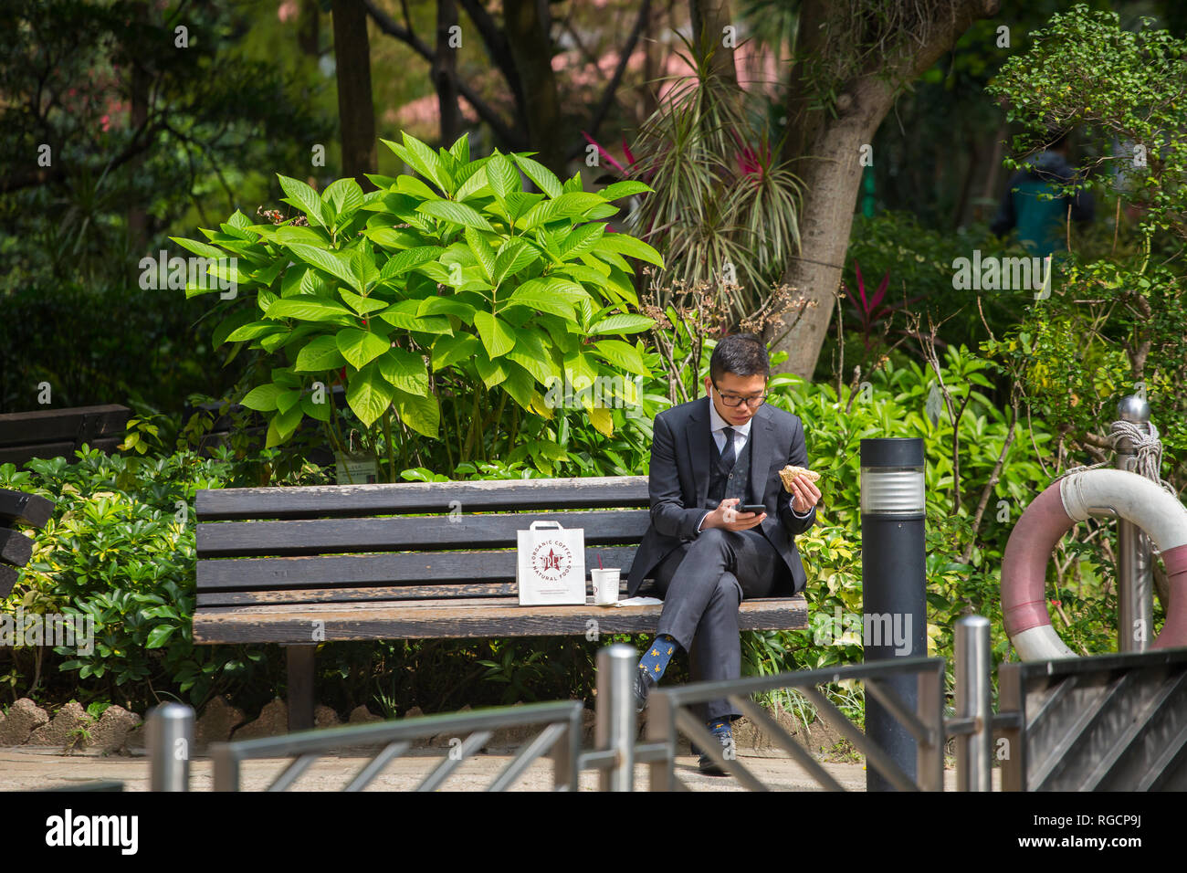 A man in suit sitting on a bench at Hong Kong Park, holding a sandwich on his hand for his outdoor lunch to recharge and relax his mind. - Stock Image
