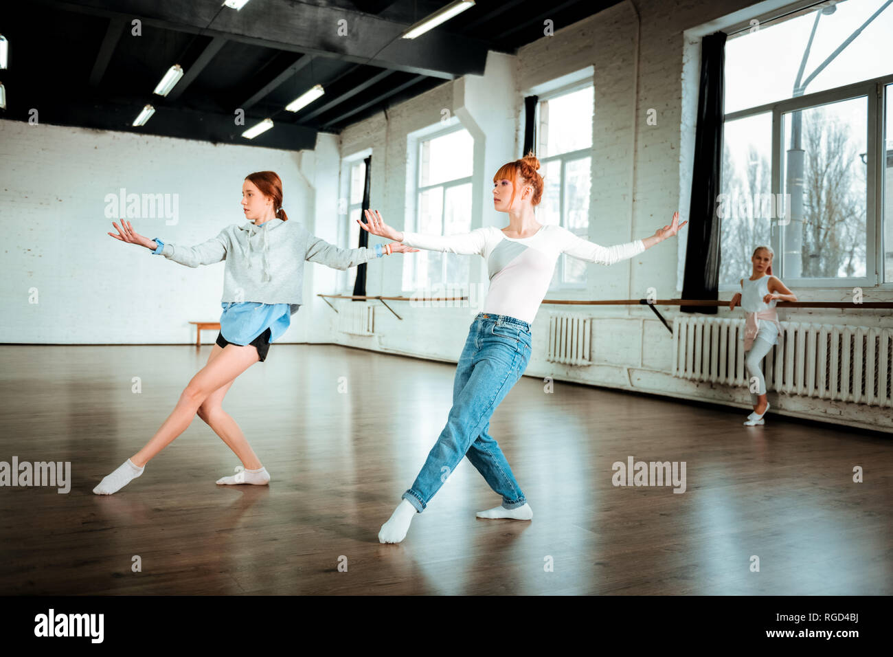 Beautiful red-haired professional dancer in blue jeans and her student dancing in the studio Stock Photo