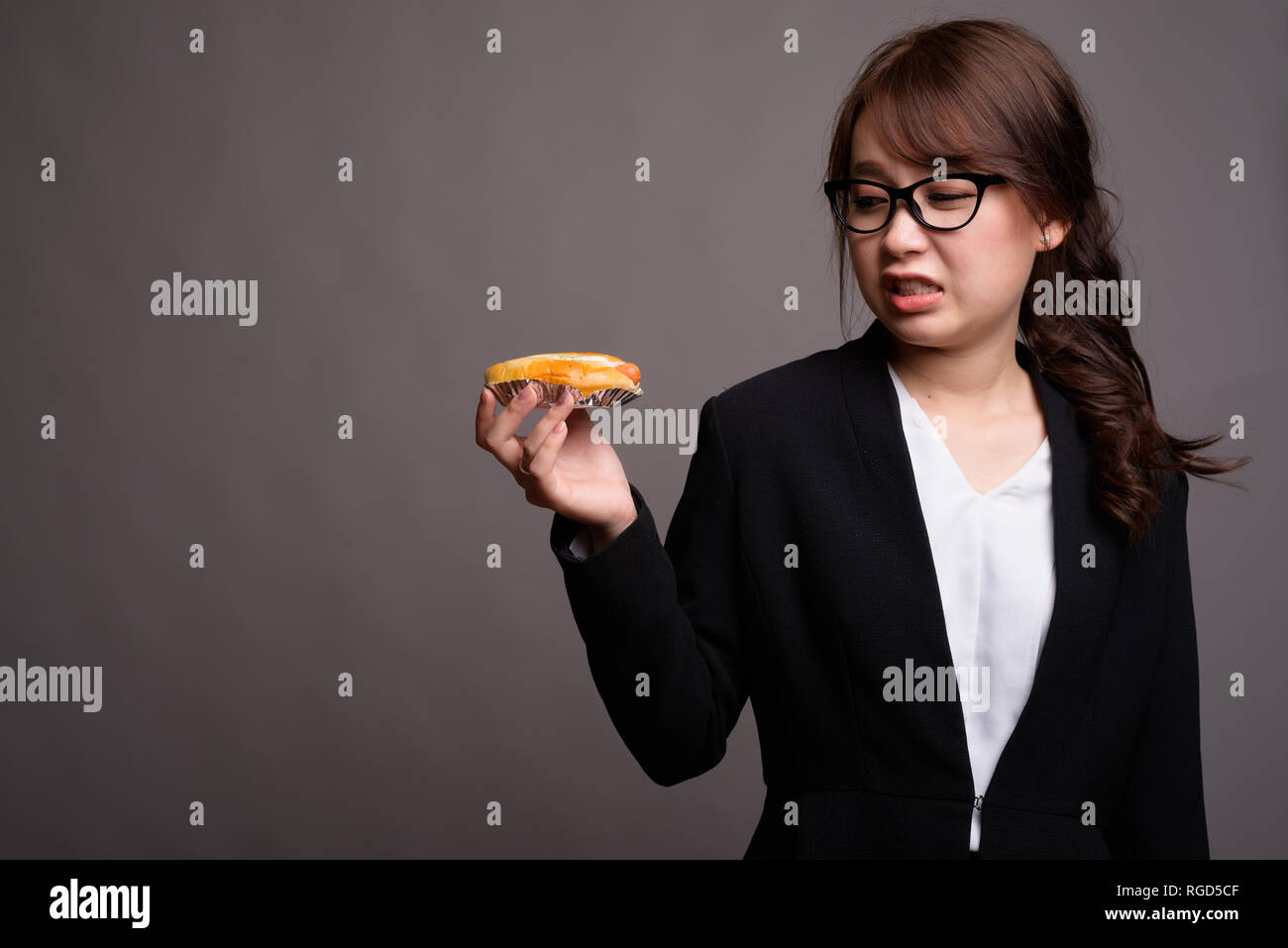 Disgusted looking Asian businesswoman holding hotdog in studio - Stock Image