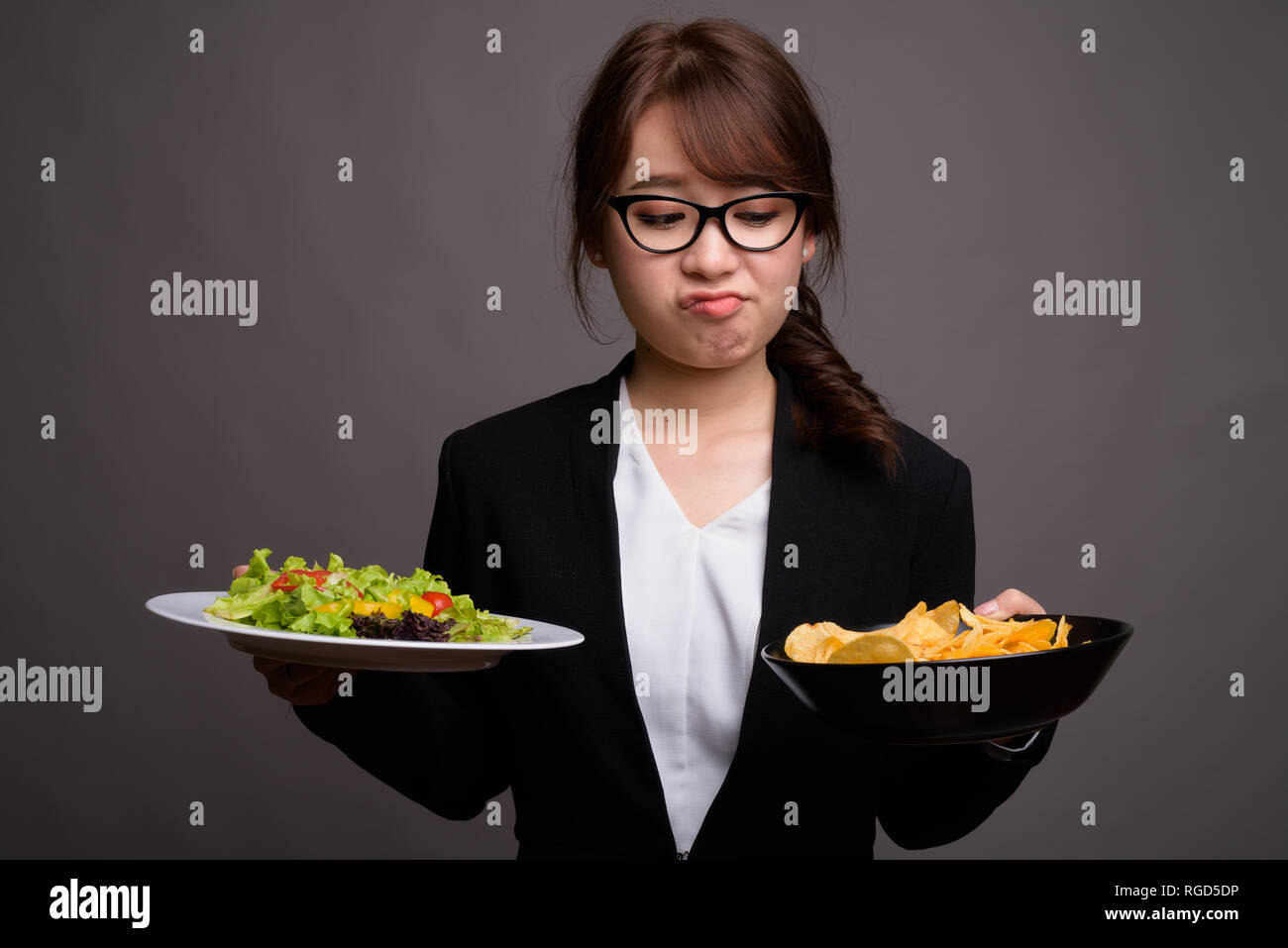 Asian businesswoman holding salad and potato chips - Stock Image