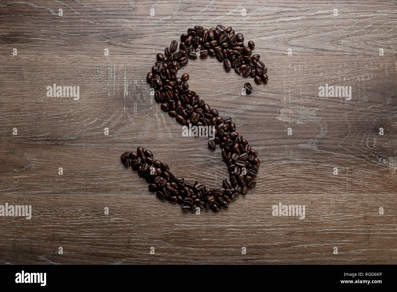Dark roasted coffee bean arranged on a wooden table in the shape of text alphabet letter S - Stock Image