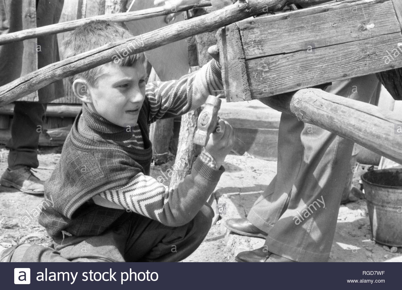 The village boy helps to his family. He nails the board that came off the wain. Boy does this job with knowledge of the matter. He's the real helper! The grandfather and father watching him. The men accustoming him to independent and adult life. - Stock Image