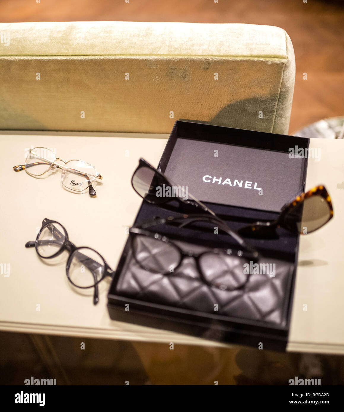 STRASBOURG, FRANCE - OCT 28, 2018: Multiple luxury Chanel, Persol and Gucci eyewear frames in a Chanel box at the optometrist optician office - Stock Image