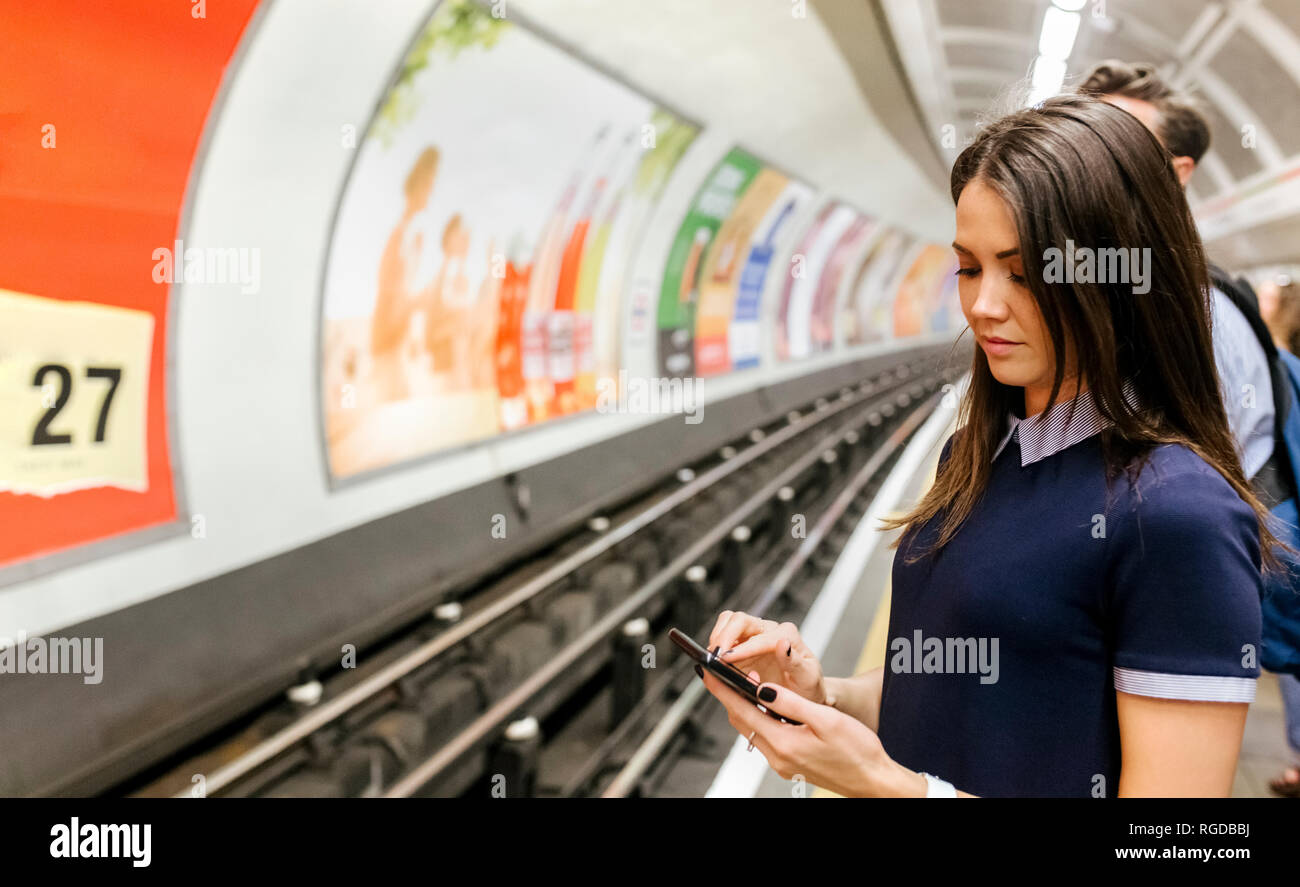 UK, London, young woman waiting at underground station platform looking at cell phone - Stock Image