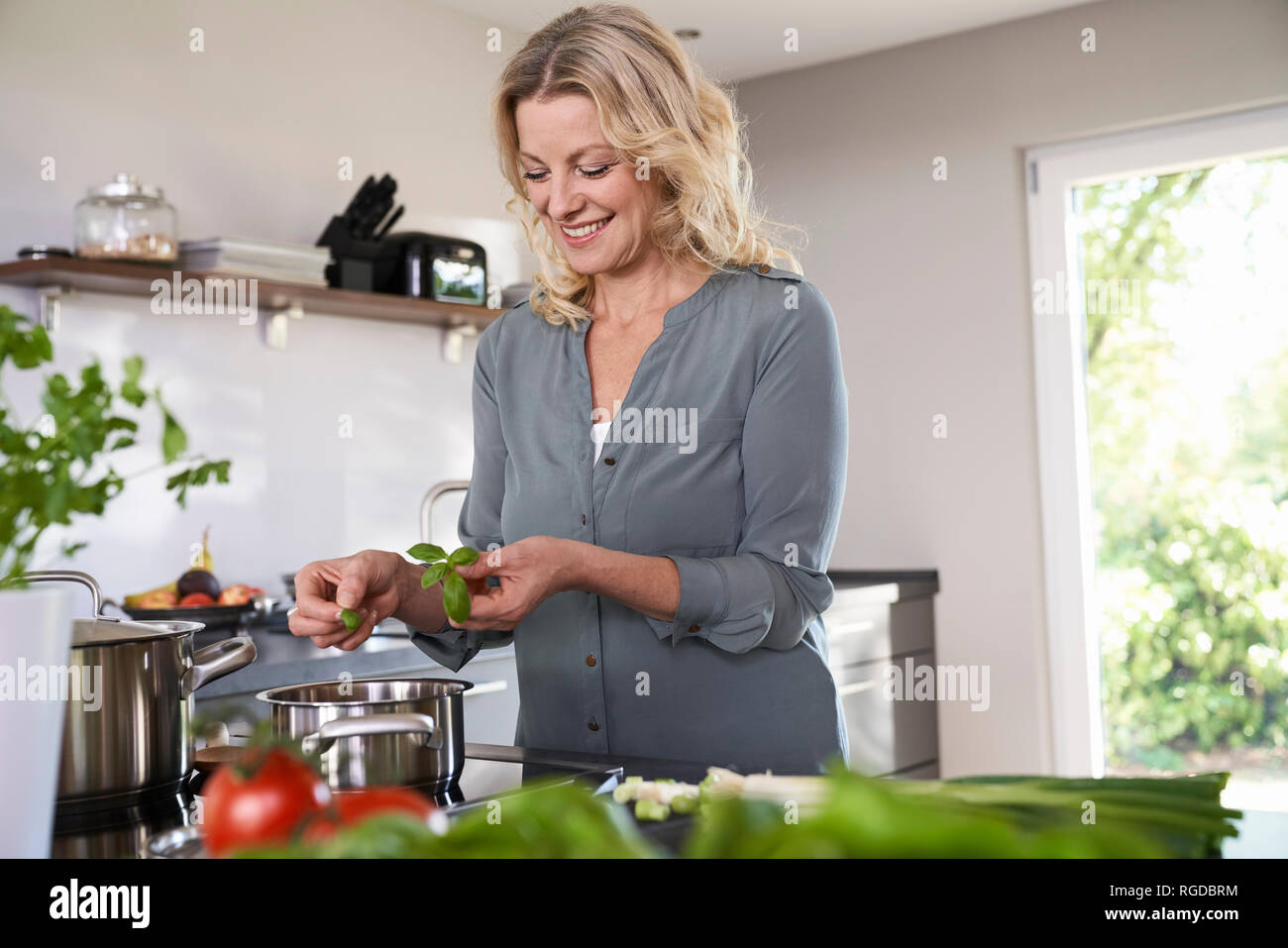 Smiling woman cooking in kitchen putting basil into cooking pot - Stock Image