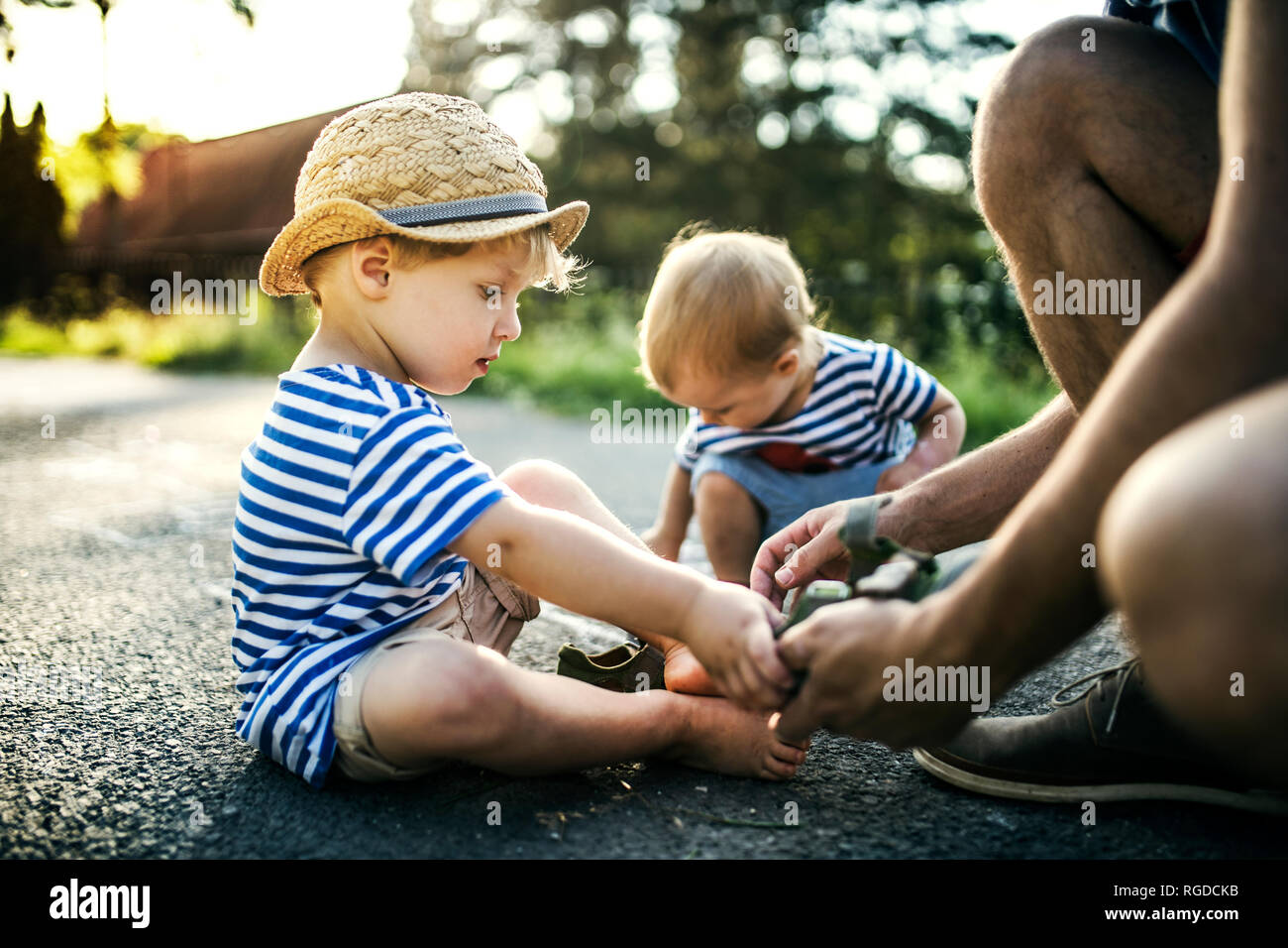 fdd566590 Father assisting his little son undressing his shoes - Stock Image