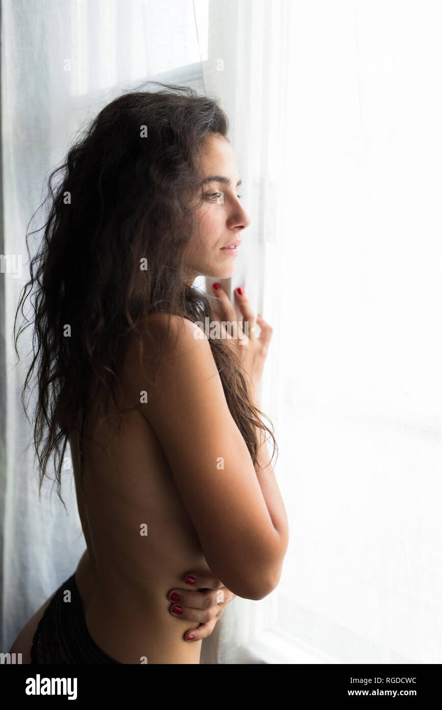 Young shirtless woman standing at the window watching something - Stock Image