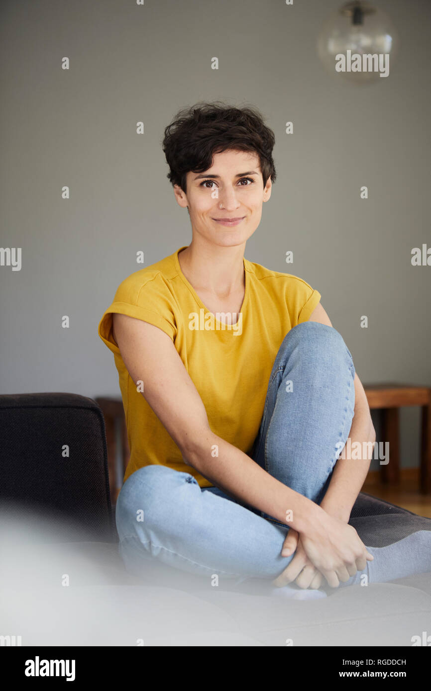 Portrait of smiling woman sitting on couch at home - Stock Image