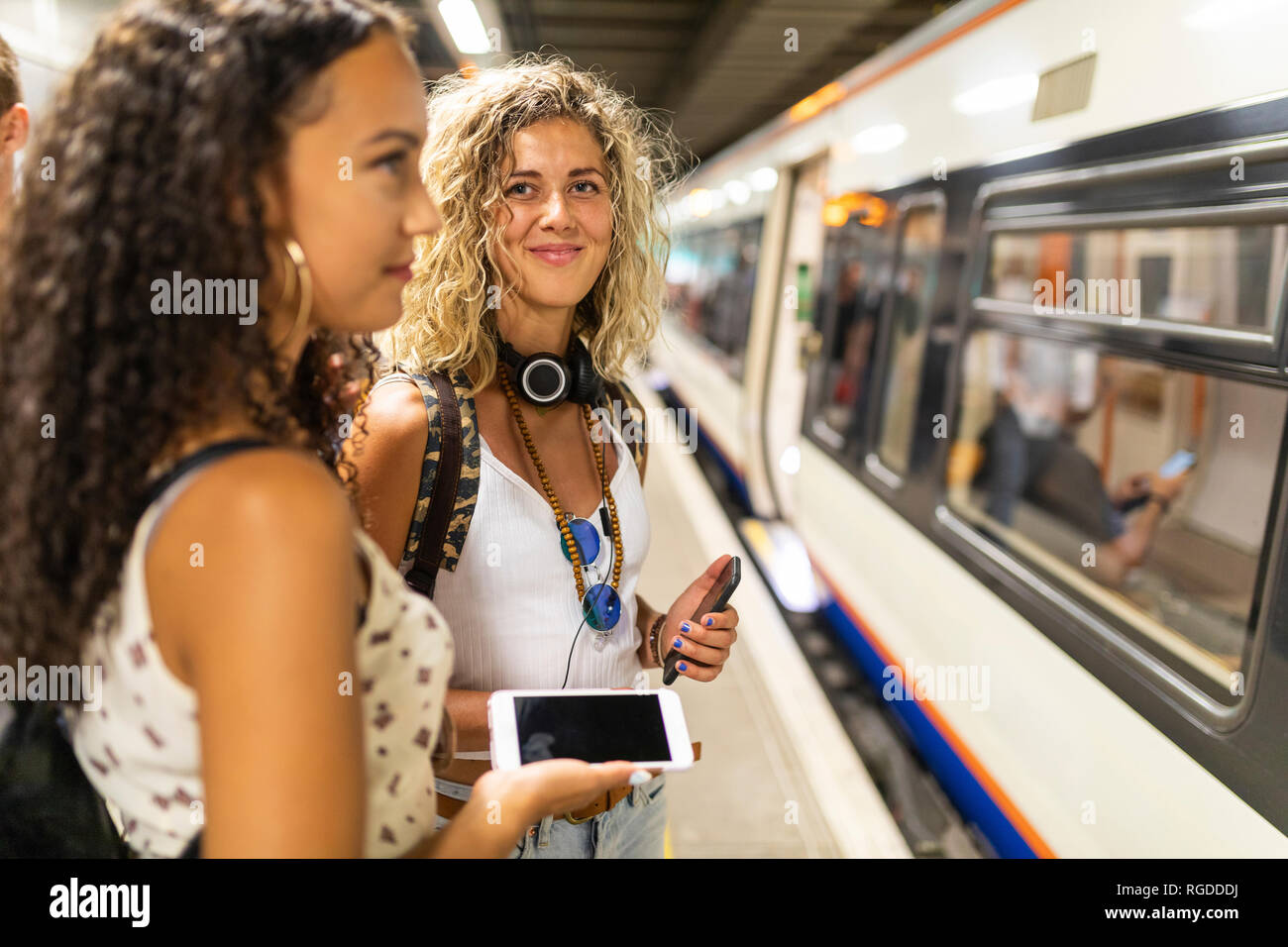 UK, London, two young women with cell phones waiting at underground station platform - Stock Image