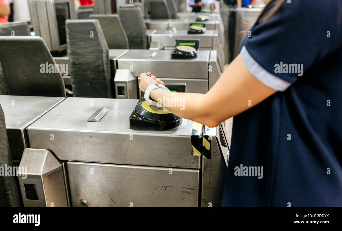 Young woman paying with her smartwatch on the subway, partial view - Stock Image