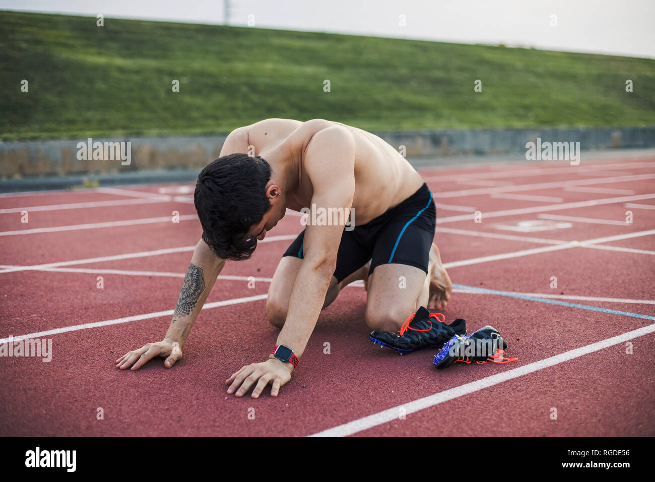 Athlete kneeling on a tartan track after finishing a race - Stock Image