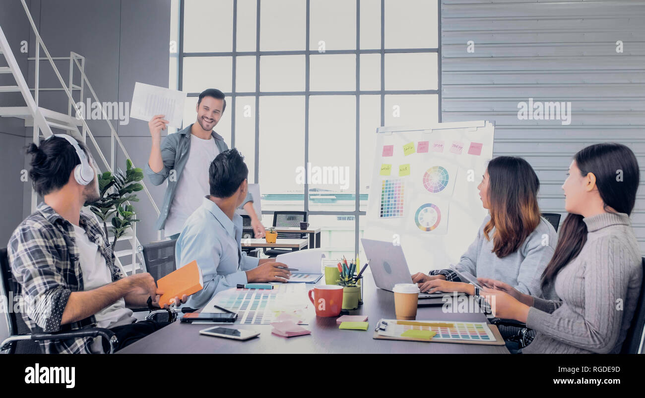 Creative director walk in to meeting and tell team a good news project at meeting room n office,high five each other. Stock Photo