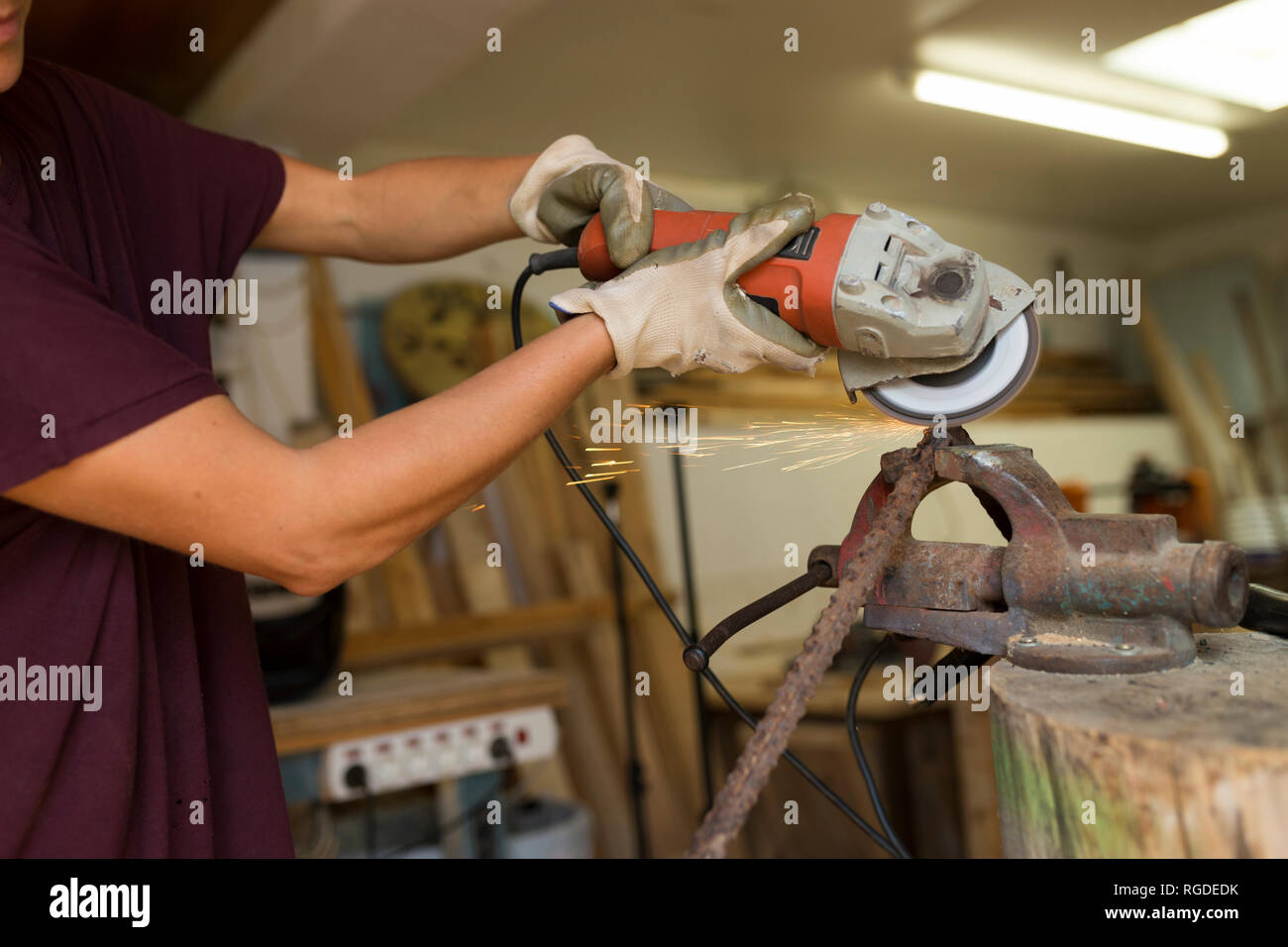 Craftswoman using angle grinder in her workshop - Stock Image