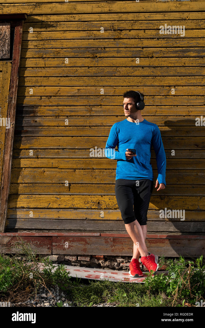 Athlete leaning against house wall with cell phone and headphones - Stock Image