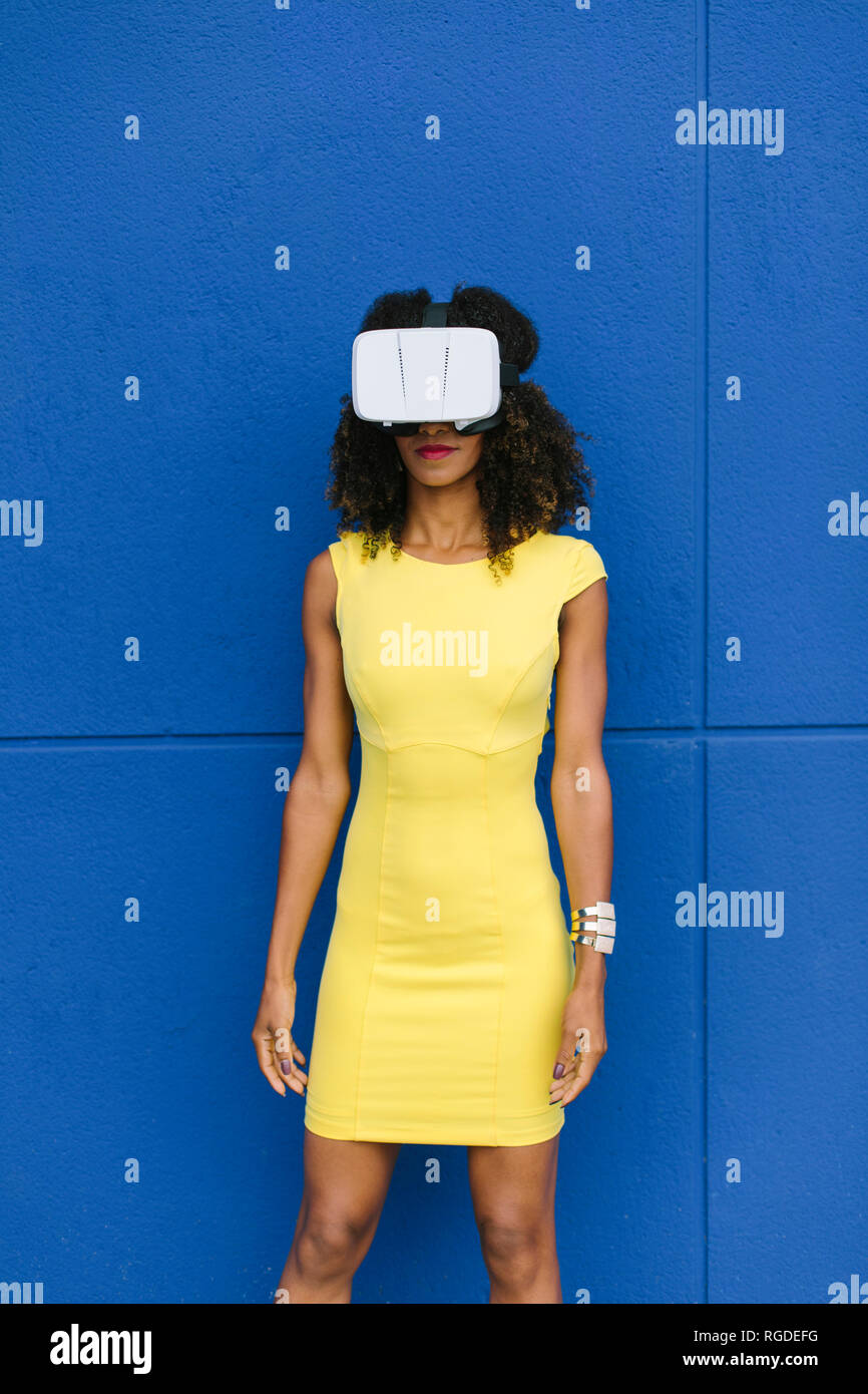 Woman in yellow dress wearing Virtual Reality Glasses against blue background - Stock Image