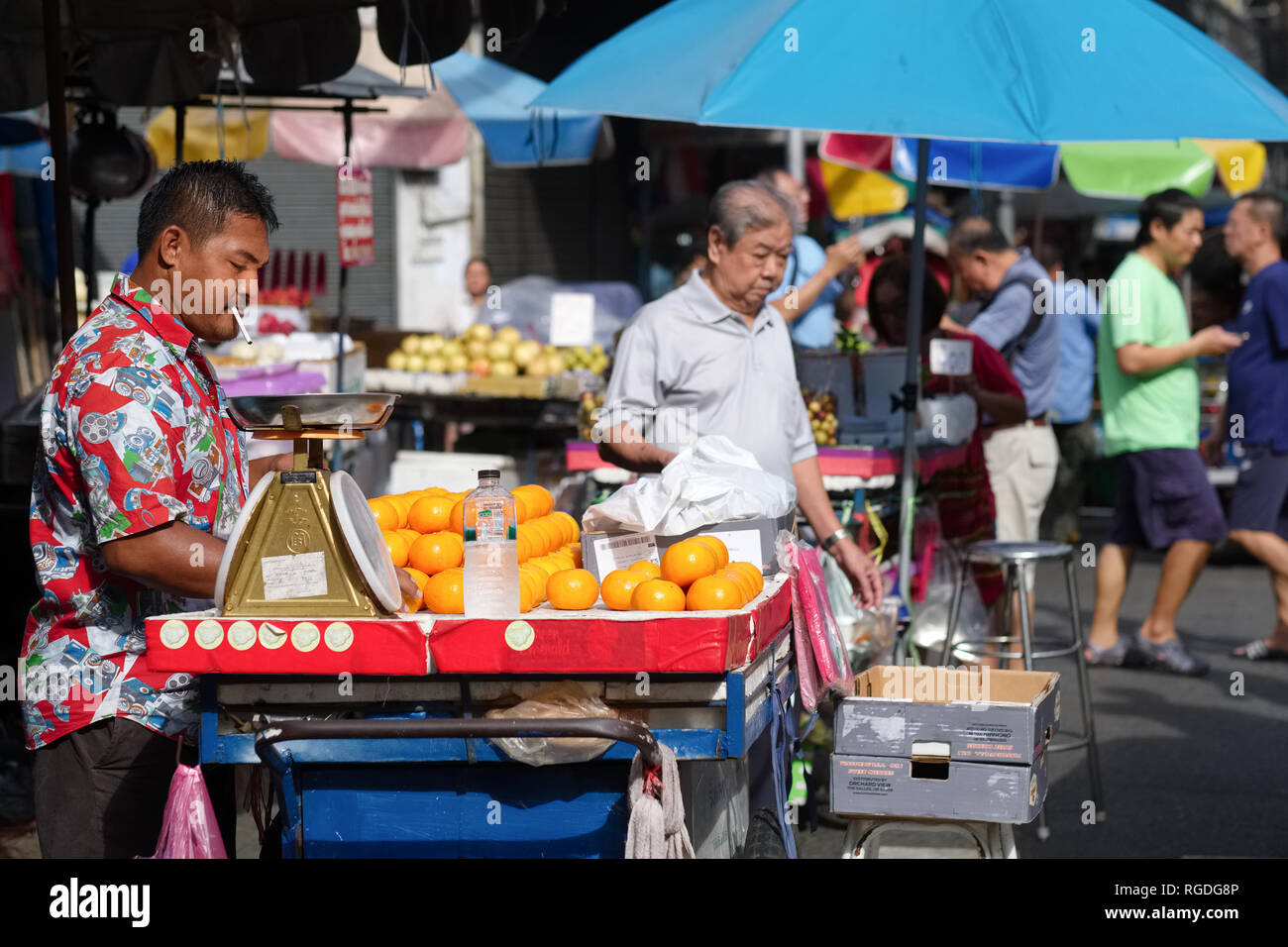 An orange vendor with his pushcart in the Old Market, Chinatown, Bangkok, Thailand - Stock Image