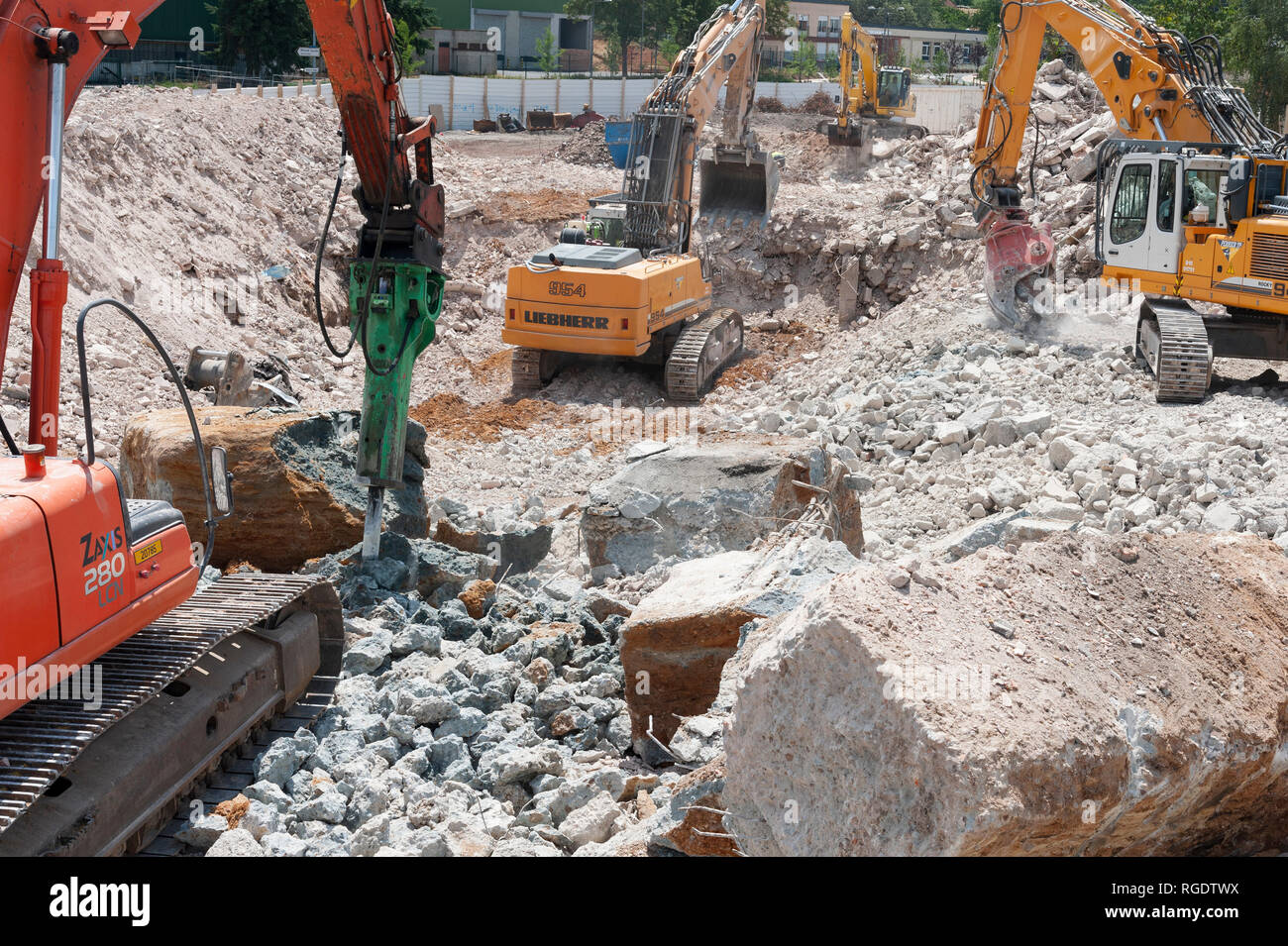 Deconstruction site. Four hydraulic excavators in action with different tools: hydrolic rock breaker (in the foreground), bucket and concrete cracker. Stock Photo