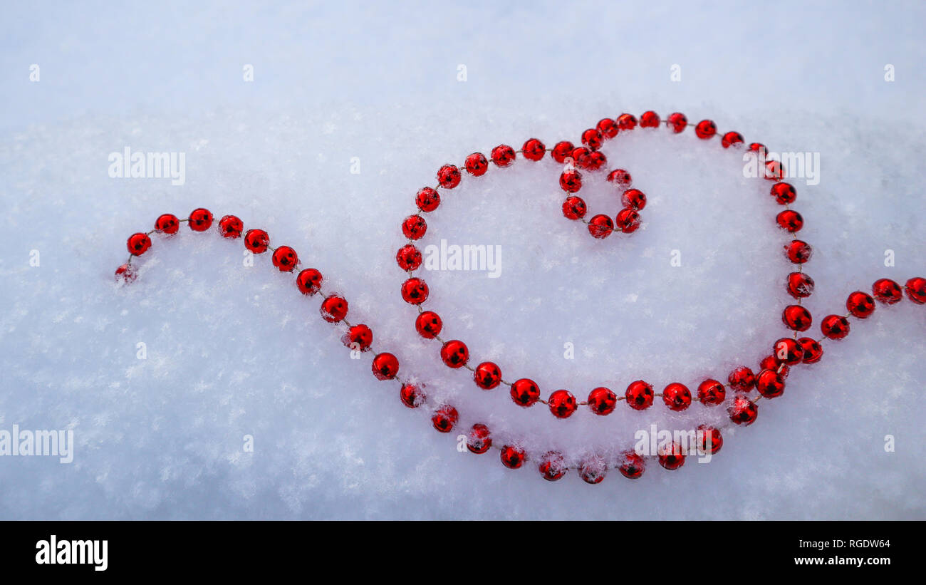 Bright red beads in shape of a heart on fresh white snow. Perfect Valentines Day, Christmas, New Year greeting card background. - Stock Image