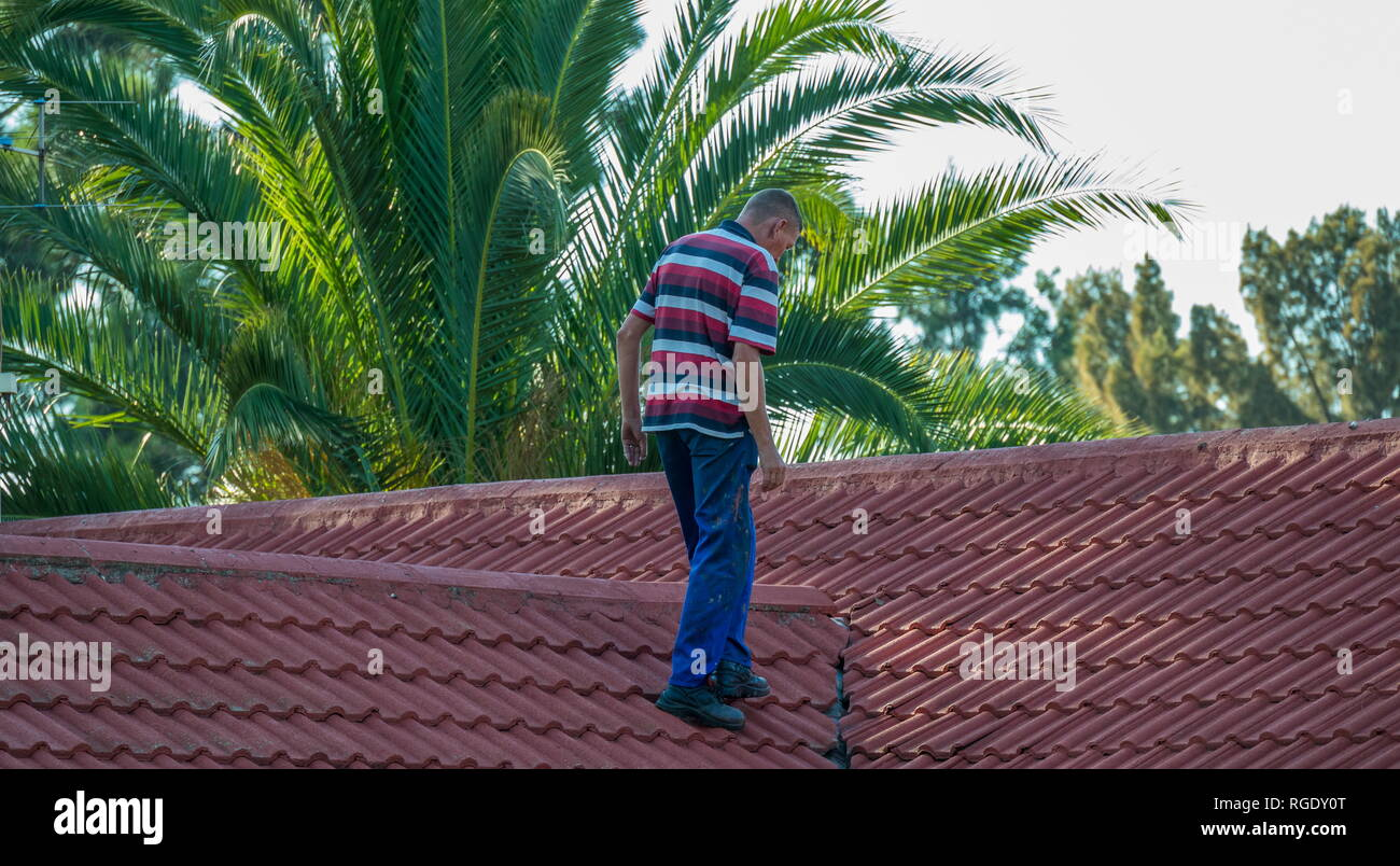 Johannesburg, South Africa - an unidentified homeowner attends to repairs to the roof of his house image with copy space in landscape format - Stock Image