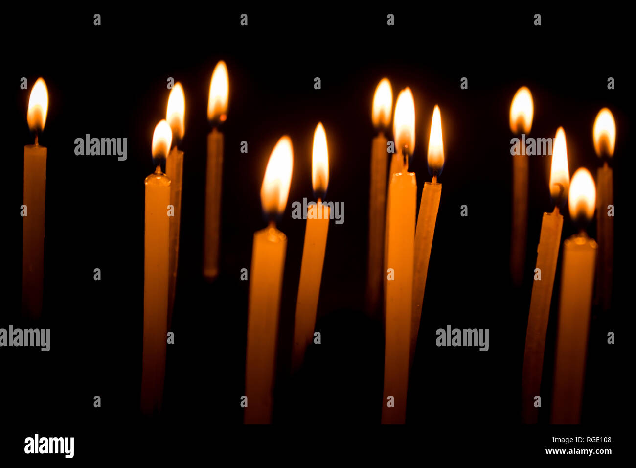 Many christmas candles burning at night on the black background. Candle flame set isolated in black background. Group of burning candles in dark with  Stock Photo