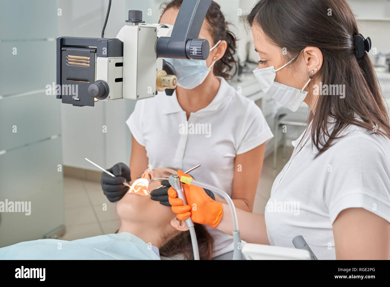 Female patient lying on dental chair while professional dentist treating teeth. Experienced doctor working with modern equipment and assistant helping. Concept of stomatology and care. - Stock Image