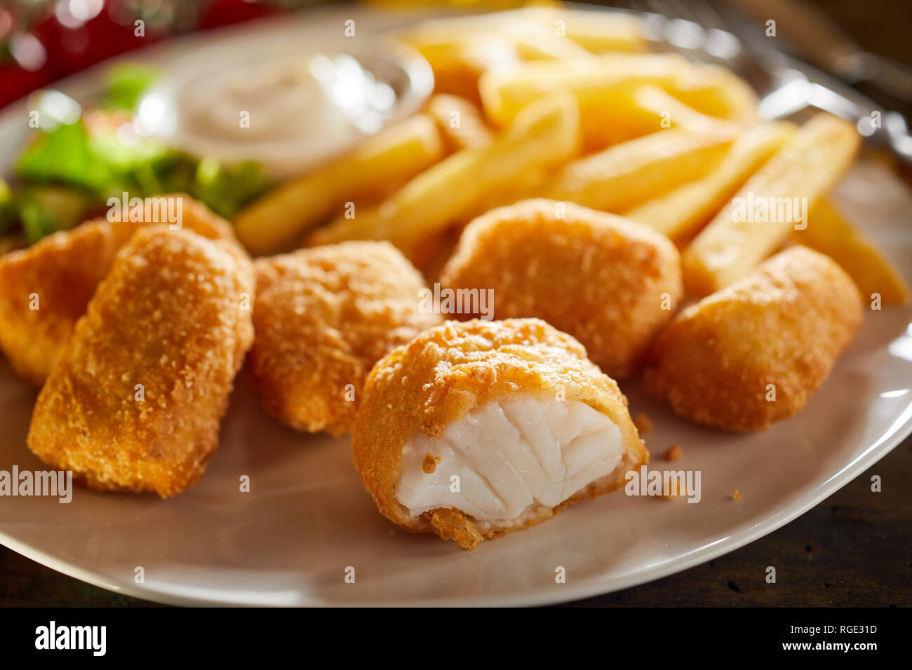 Tasty seafood appetiser of fried kibbeling, a Dutch recipe of bite size portions of breaded cod served with potato chips and salad - Stock Image
