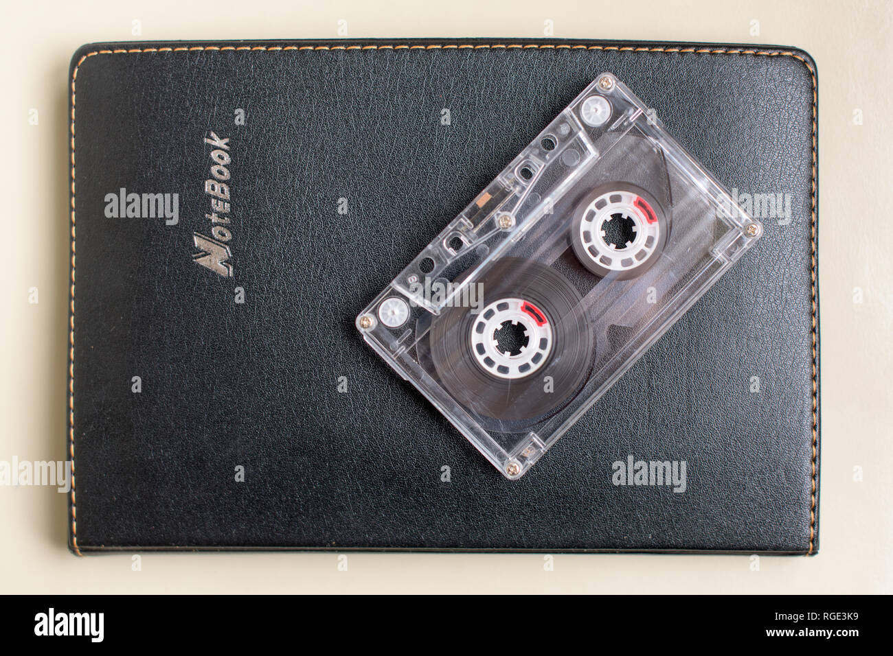 One Plastic cassette on a black notebook - Stock Image