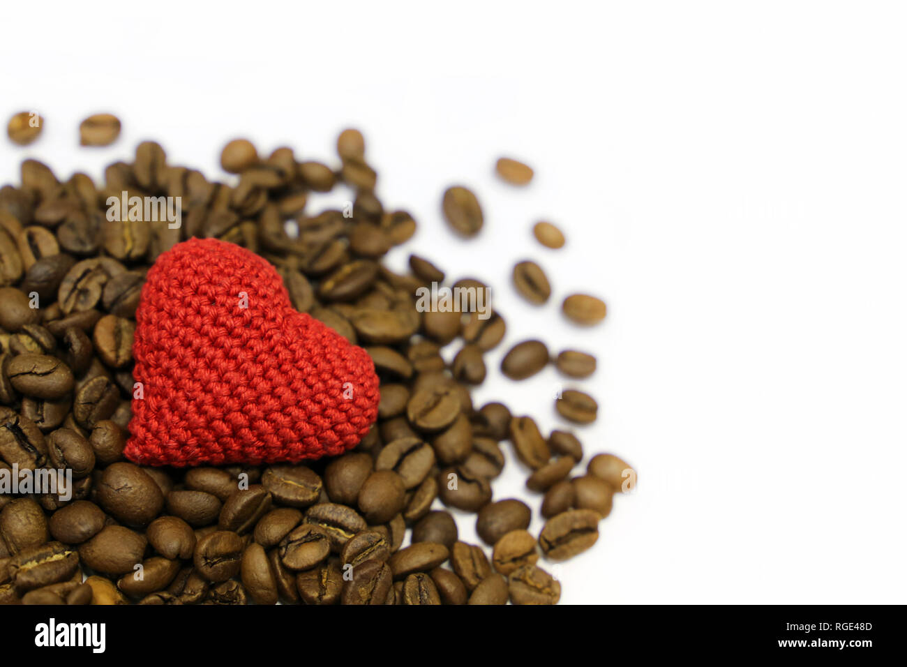 Love to coffee, Valentine heart and roasted coffee beans isolated on white background. Red knitted symbol of love, concept of romantic breakfast Stock Photo