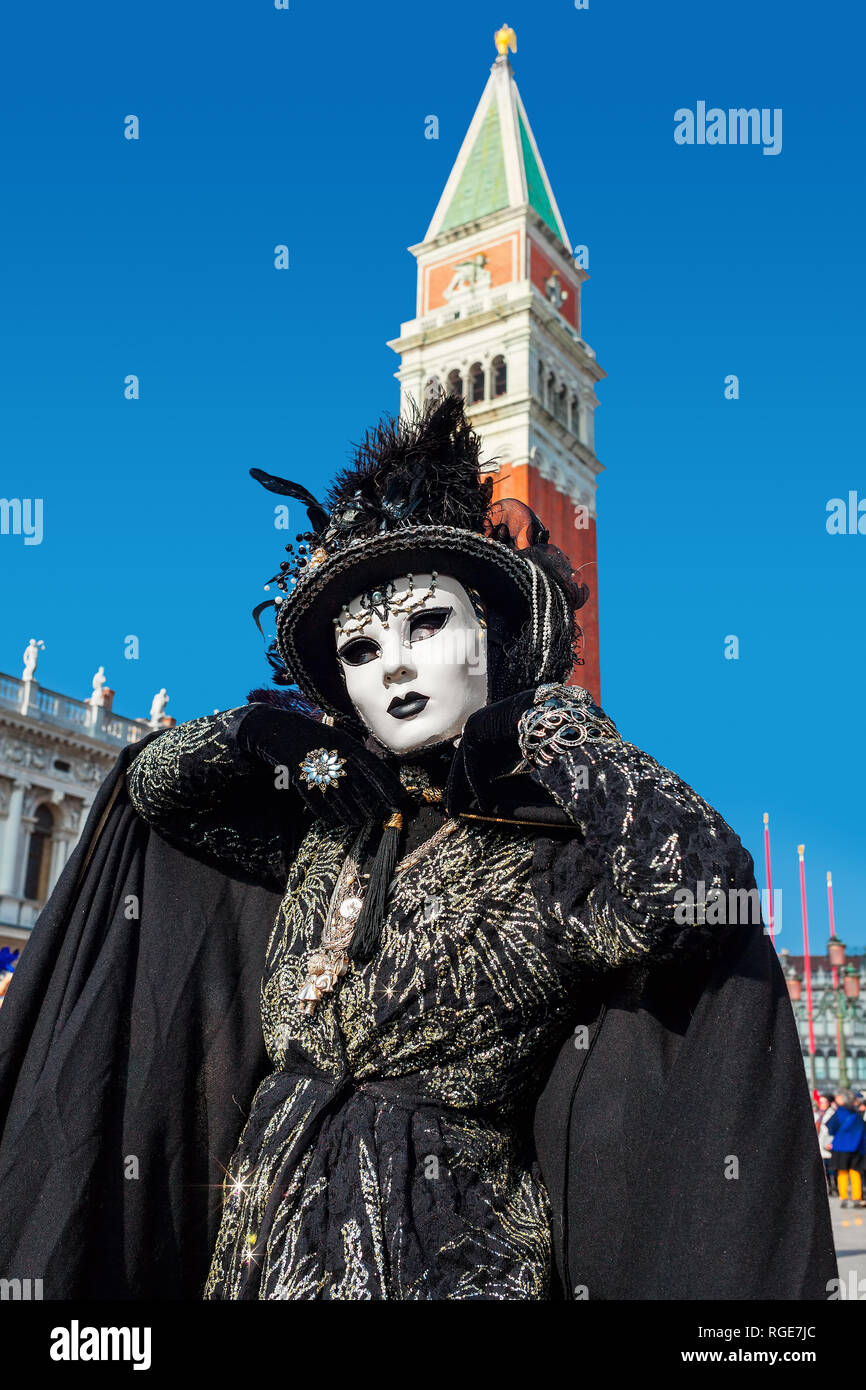 Vertical oriented portrait of an unidentified woman weared in vintage black costume, gloves, hat and white mask on San Marco square in Venice. - Stock Image