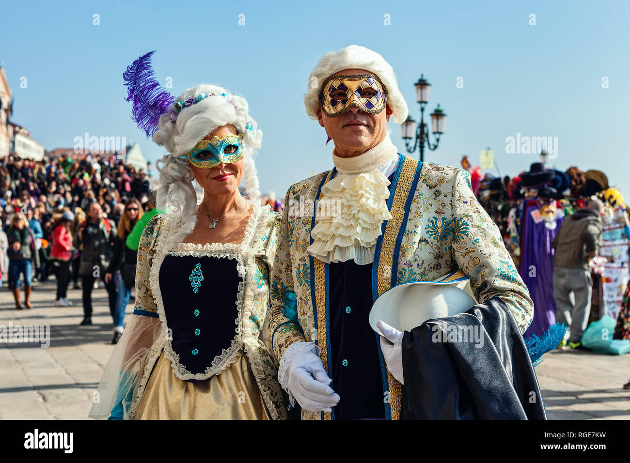 Couple of unidentified participants wear vintage colorful costumes and masks during famous traditional Carnival in Venice, Italy. Stock Photo